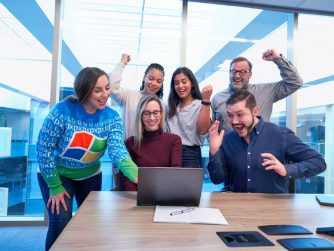 Third Culture Africa 4 start up business success stories to learn from a group of joyful people in a boardroom looking at a laptop place on a brown table