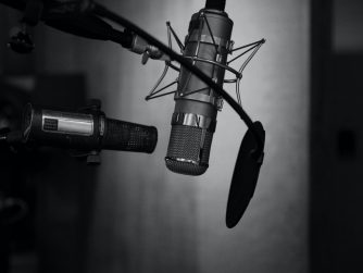 Third Culture Africa 7 Ways to use a Podcast for an entrepreneur podcast microphones with one having pop shield and facing up side down in a room with black background