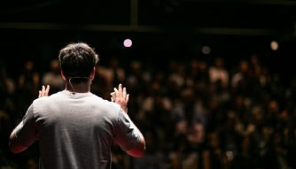 6 things every career coach wants you to know third culture Africans man talking to the crowd with his 2 hands lifted