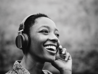 Third Culture Africans podcast woman listening to podcast on headphones