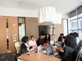 Third-Culture-Africa 5 things famous entrepreneurs have in common women having meeting in a boardroom with their laptop place on a brown table and a tv place the brown ward close a brown closet.