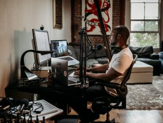 Third Culture Africa 6 Essential Pieces Of Podcast Equipment You Need For Success a man wearing a cream t-shirt sitting on a brown office chair in front of a desk with speakers attached and laptop and mixer on the table with headphones on his neck