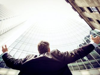Third Culture Africa 6 leadership skill for success a man in a black suit with blue sky shirt and a blond hair facing a tall building with his arm wide open