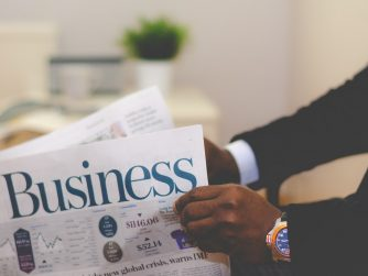 Third Culture Africa 7 leadership principles from famous entrepreneurs a man wearing black suit and white shirt with a blue wrist watch is holding a newspapper on which the word business is written