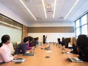 Third Culture Africa Transformational Leadership a group of people in boardroom with laptops and note books on a brown table all facing one direction to a woman writing on a white board